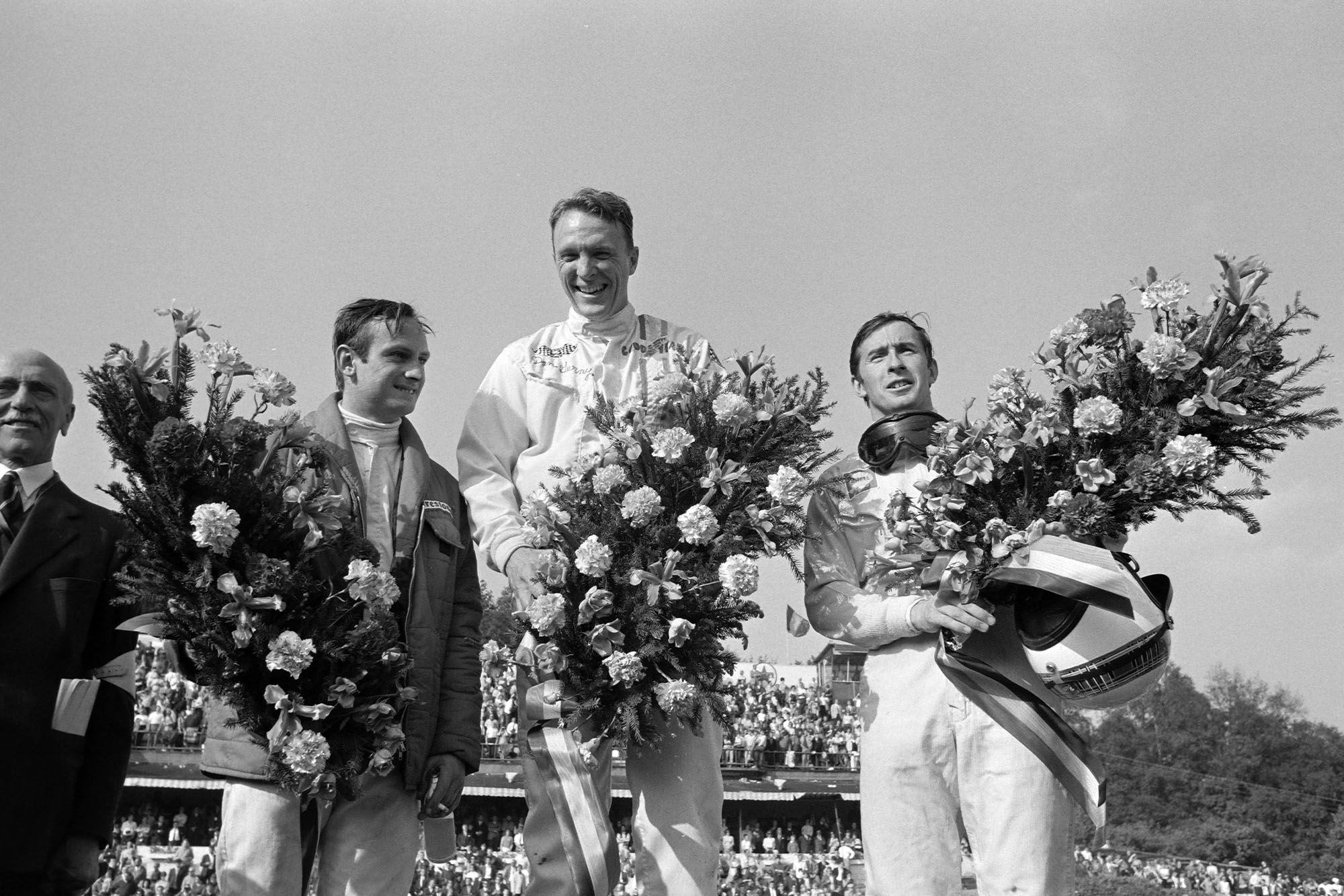 Dan Gurney, 1st position, Jackie Stewart, 2nd position, and Chris Amon, 3rd position, celebrate on the podium.