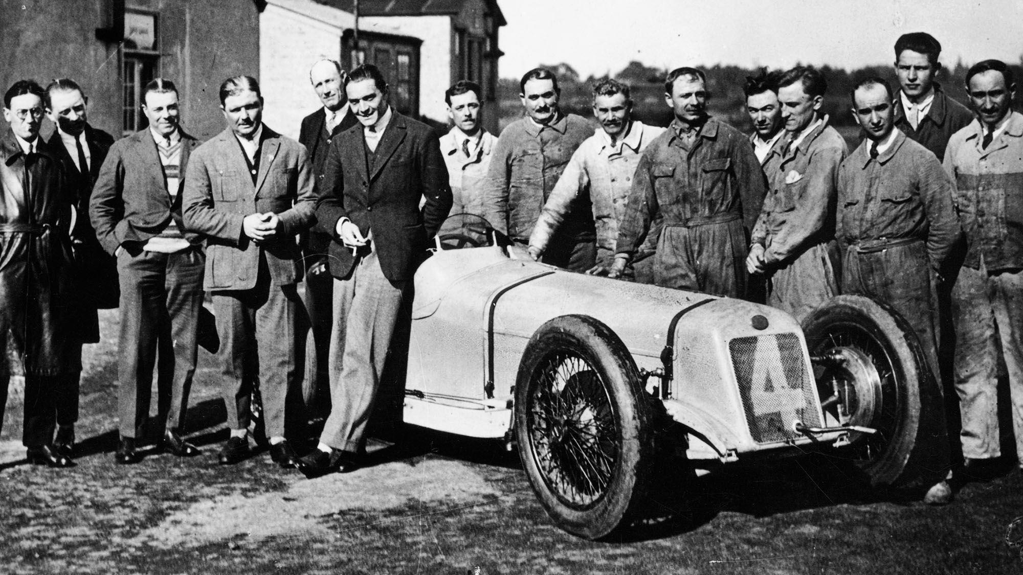 Robert Benoist with a cigarette, leaning against a Delage 15-S8, 1927. A group of mechanics stand to the right of the car. The racing drivers Albert Divo and Edmond Bourlier stand to the left of Benoist; Divo immediately to the left of him, and Bourlier to the left of Divo. In 1927 Benoist won the French, Spanish, European and British Grand Prix in a Delage 15-S8. (Photo by National Motor Museum/Heritage Images/Getty Images)