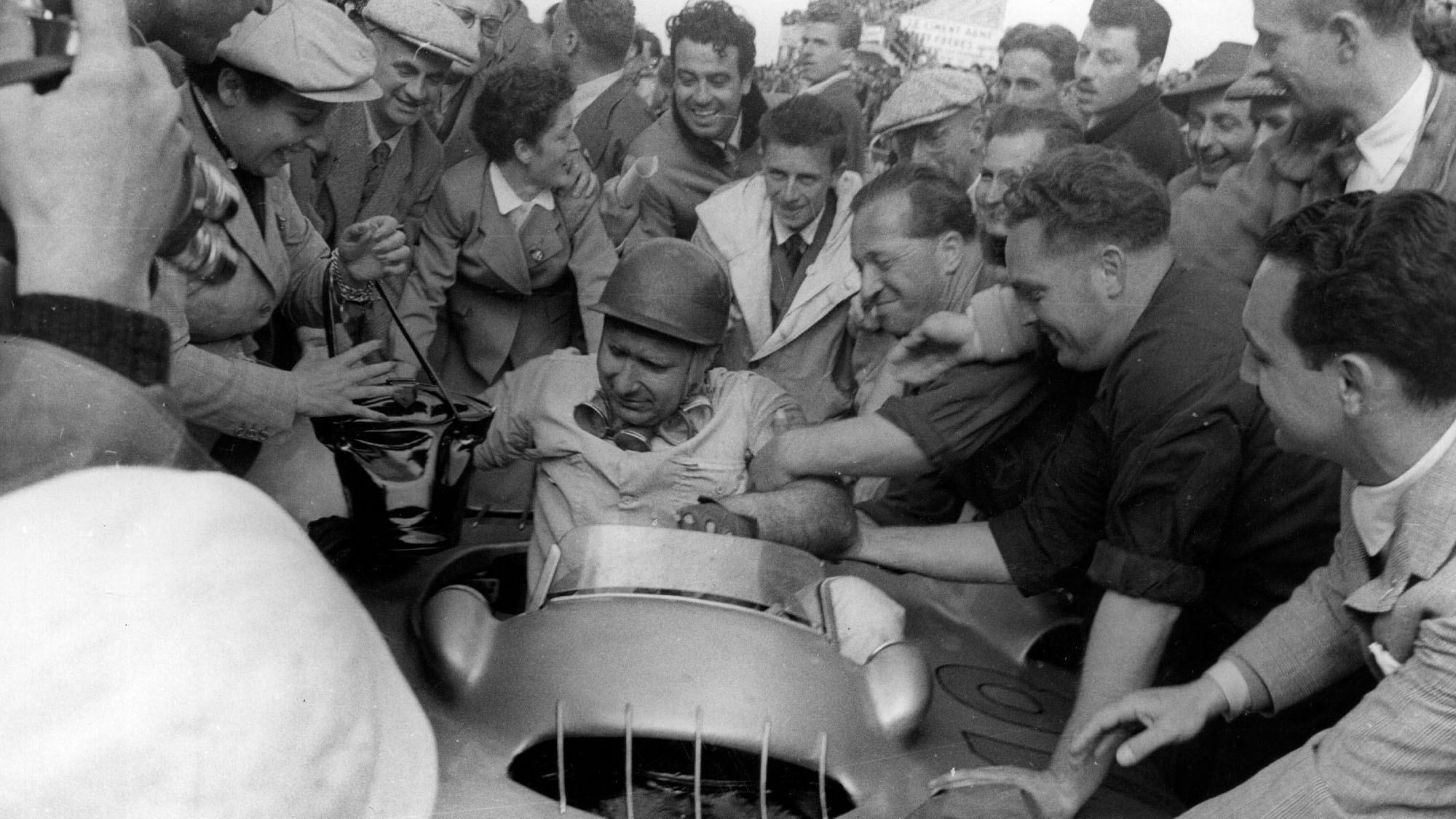 17th July 1954: Racing driver Juan Manuel Fangio (1911- 1995), receiving congratulations after winning the French Grand Prix at Reims in a Mercedes car. Original Publication: Picture Post - 7209 - First Race Of The Mercedes - A Ruthless Triumph - pub. 1954 (Photo by Joseph McKeown/Picture Post/Hulton Archive/Getty Images)