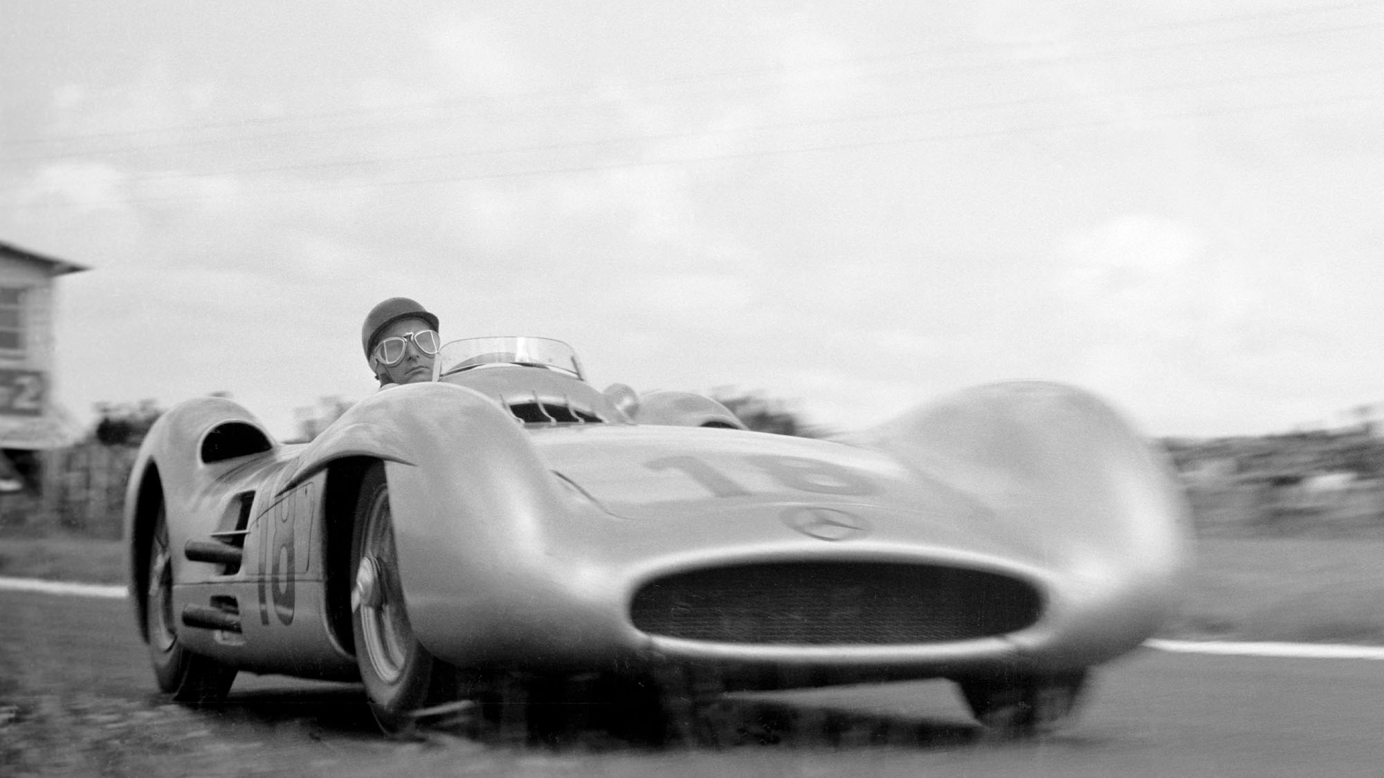 The French Grand Prix; Reims, July 4, 1954. At this race Mercedes introduced their new streamlined W196 Grand Prix cars. The new machine was victorious in this its first outing, with Juan Manuel Fangio, seen here in the ultra-fast right hand bend after the start/finish line, the easy winner ahead of his colleague Karl Kling and the privately-entered Ferrari of Robert Manzon. To some motor racing observers, it was almost as if Mercedes had come back right where they had left off in 1939. Lying on the ground right at the apex, Klemantaski captures Fangio's concentrational sangfroid perfectly. (Photo by Klemantaski Collection/Getty Images)