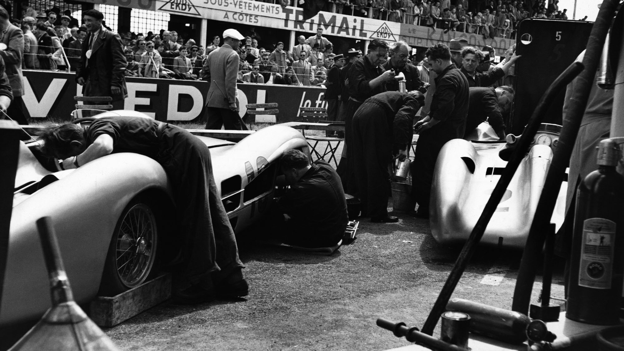 Pit mechanics work on the Mercedes-Benz racecars which are competing well in the French Grand Prix. (Photo by © Hulton-Deutsch Collection/CORBIS/Corbis via Getty Images)