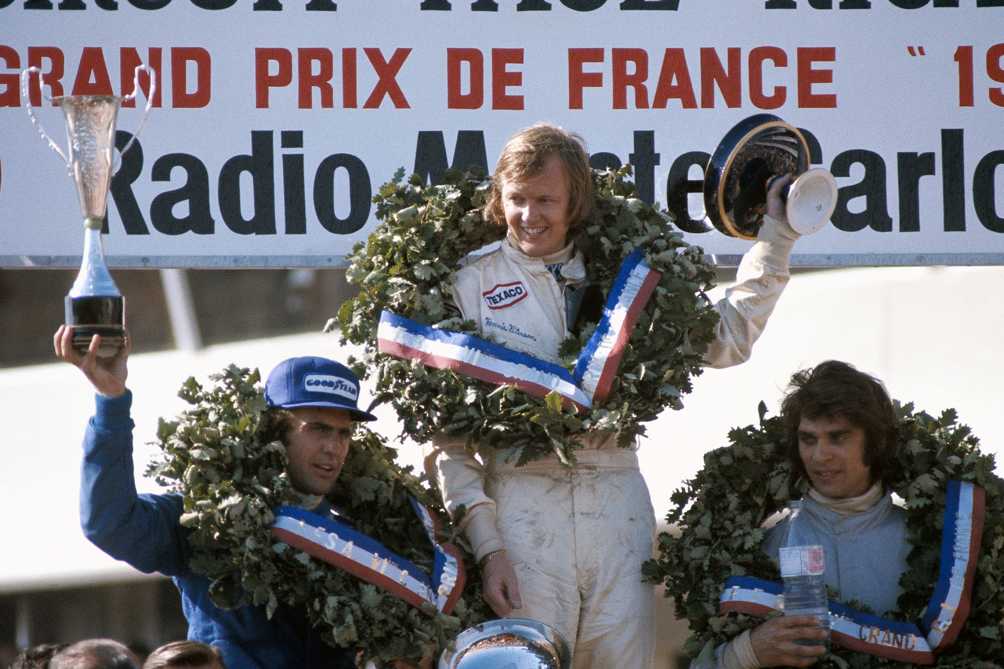 Ronnie Peterson celebrates his win on the podium at the 1973 French Grand Prix, Paul Ricard.