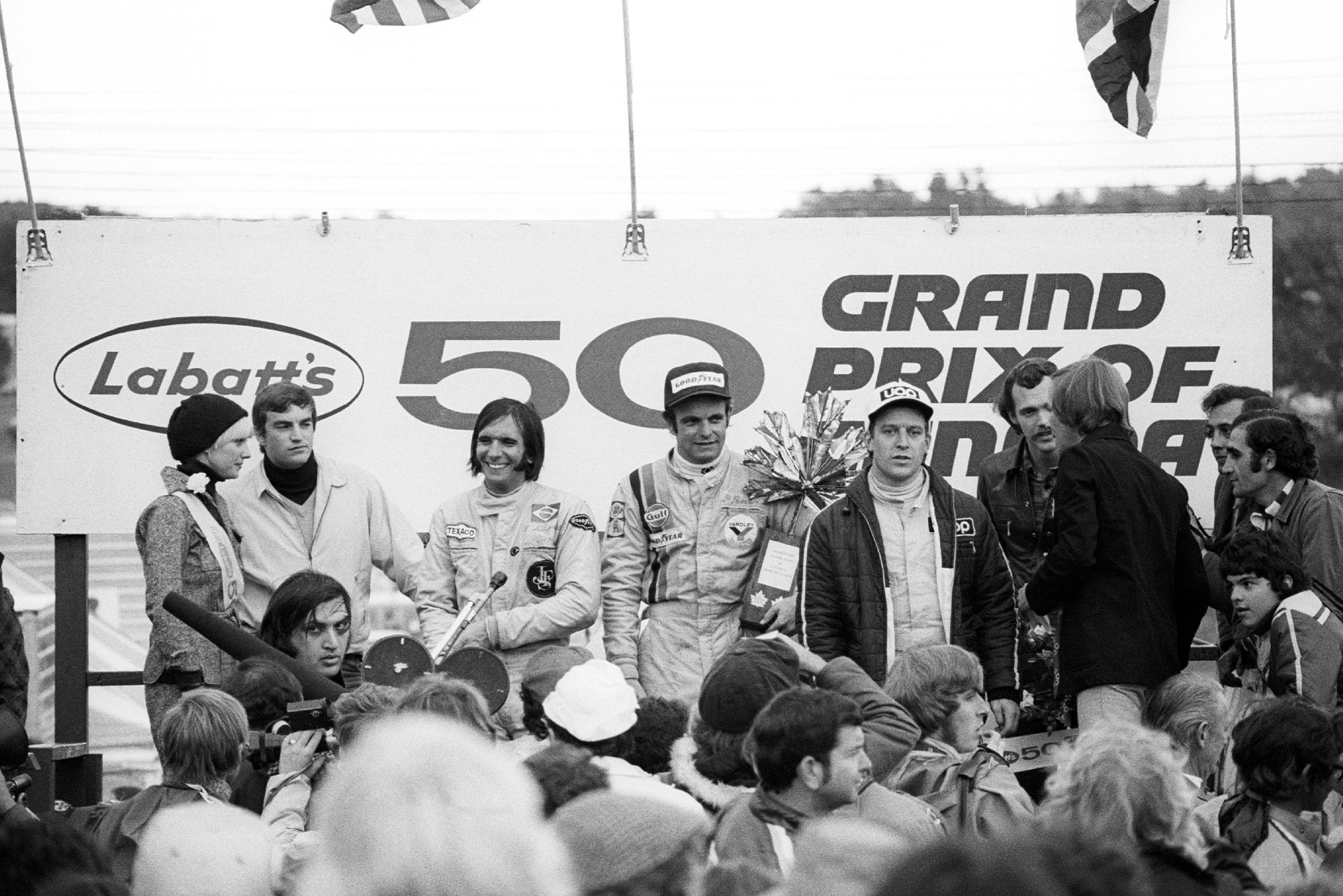 Peter Revson (McLaren) celebrates on the podium afer winning the 2973 Canadian Grand Prix, Mosport Park.