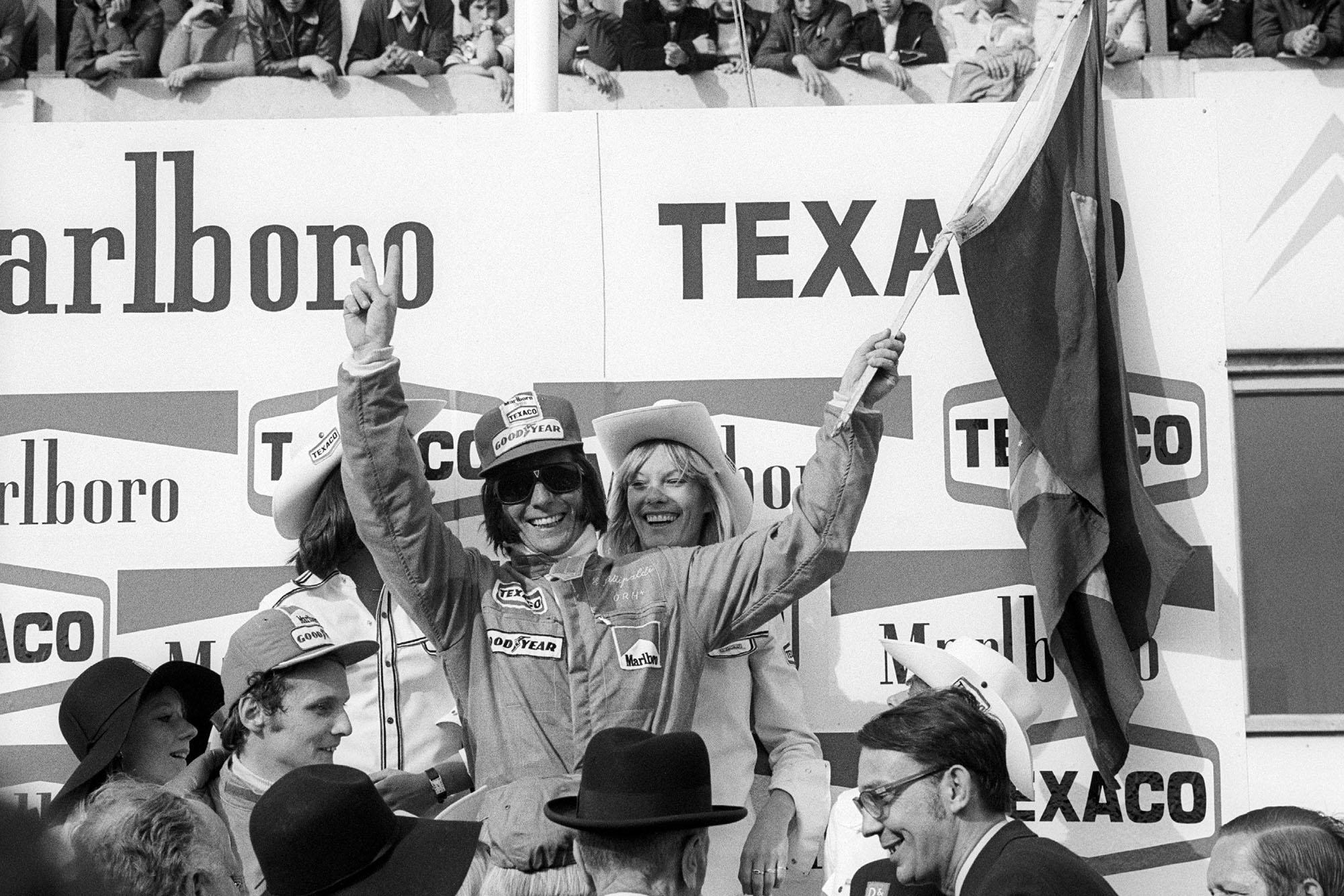 Emerson Fittipaldi celebrates his win on the podium at the 1974 Brazilian Grand Prix