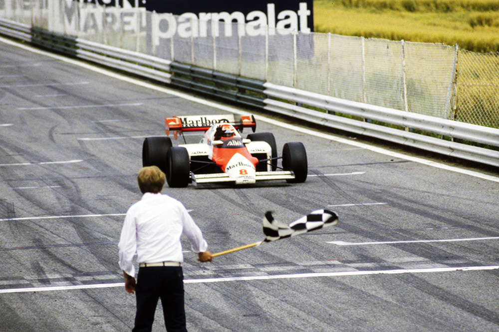 Niki Lauda in his McLaren MP4-2 TAG, crosses the finish line and takes the chequered flag to become the first Austrian driver to win the Austrian Grand Prix during the Austrian GP at Red Bull Ring.