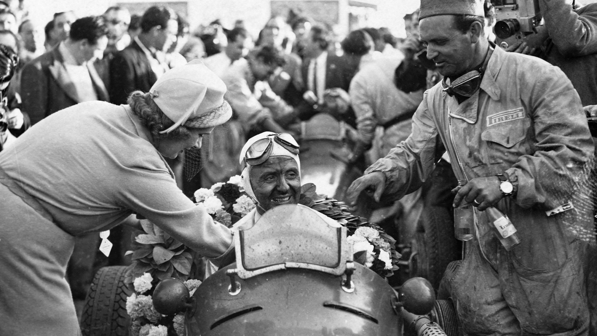 Lady Howe puts a wreath around Luigi Villoresi in his Maserati racecar after he won the International Grand Prix. (Photo by © Hulton-Deutsch Collection/CORBIS/Corbis via Getty Images)