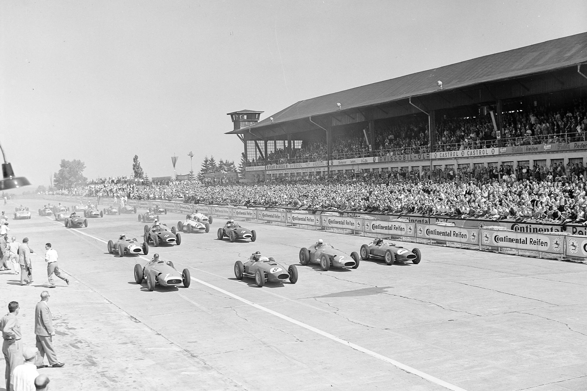 Juan Manuel Fangio, Maserati 250F, alongside Mike Hawthorn, Ferrari D50 (#8), Jean Behra, Maserati 250F (#2), and Peter Collins, Ferrari D50 (#7), at the start of the 1957 German Grand Prix, Nurburgring.
