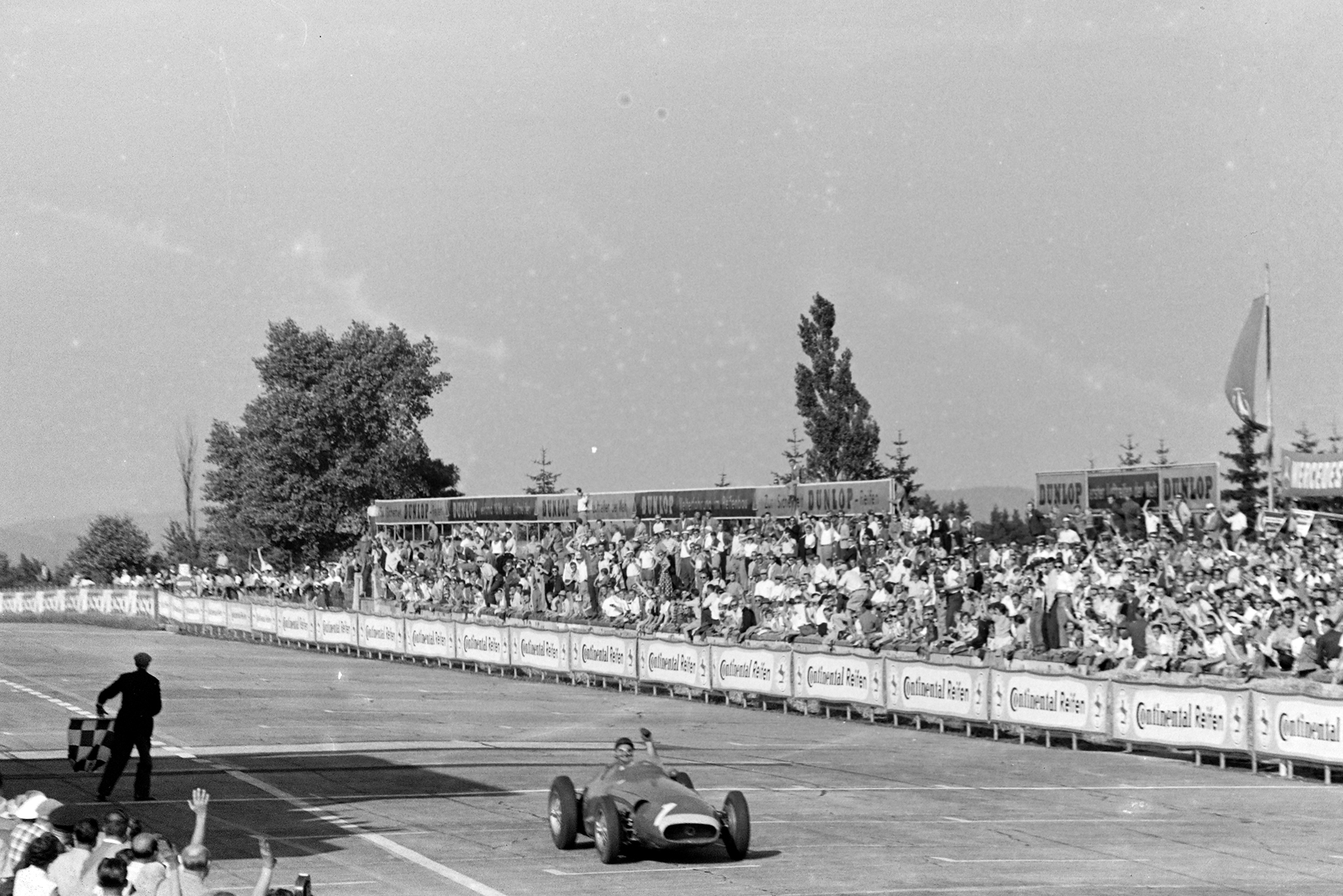 Juan Manuel Fangio crosses the finishing line and passes the chequered flag in his Maserati 250F