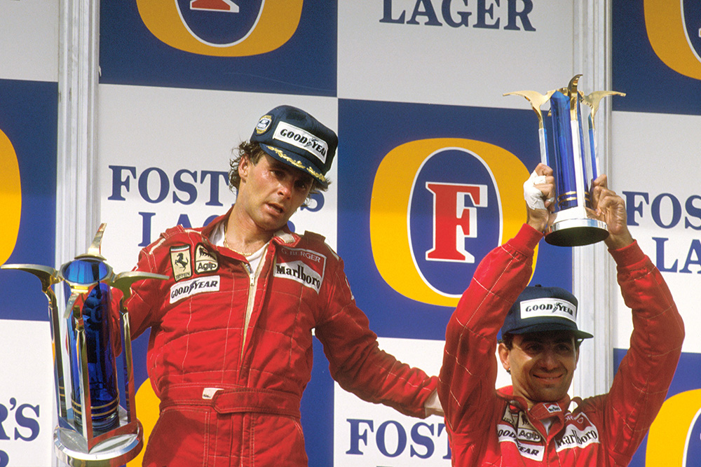 Gerhard Berger, 1st position gives teammate Michele Alboreto, 3rd position (both Ferrari) a pat on the back whilst on the podium.