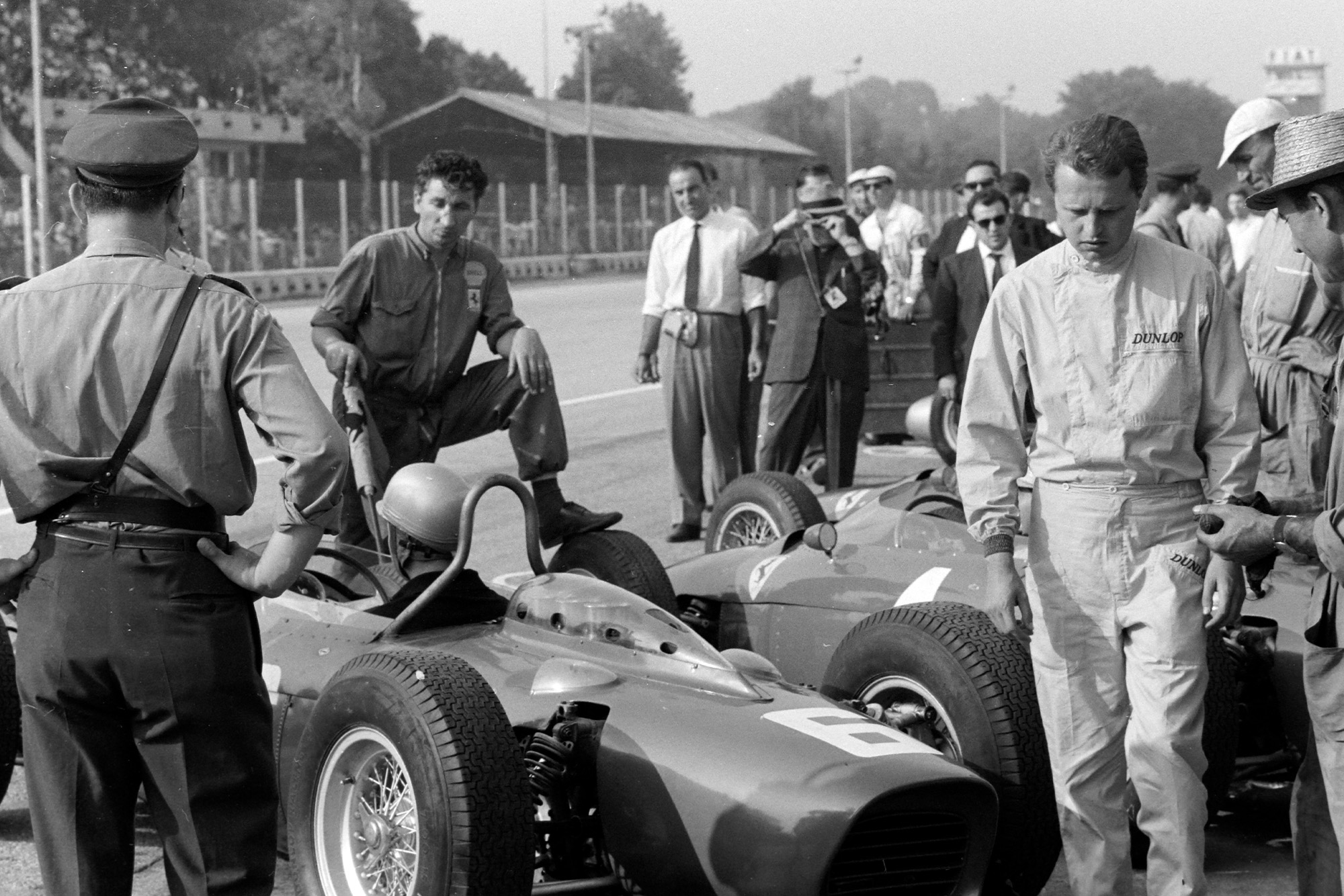 Bandini prepares to leave the Ferrari pit as team-mate Baghetti walks by