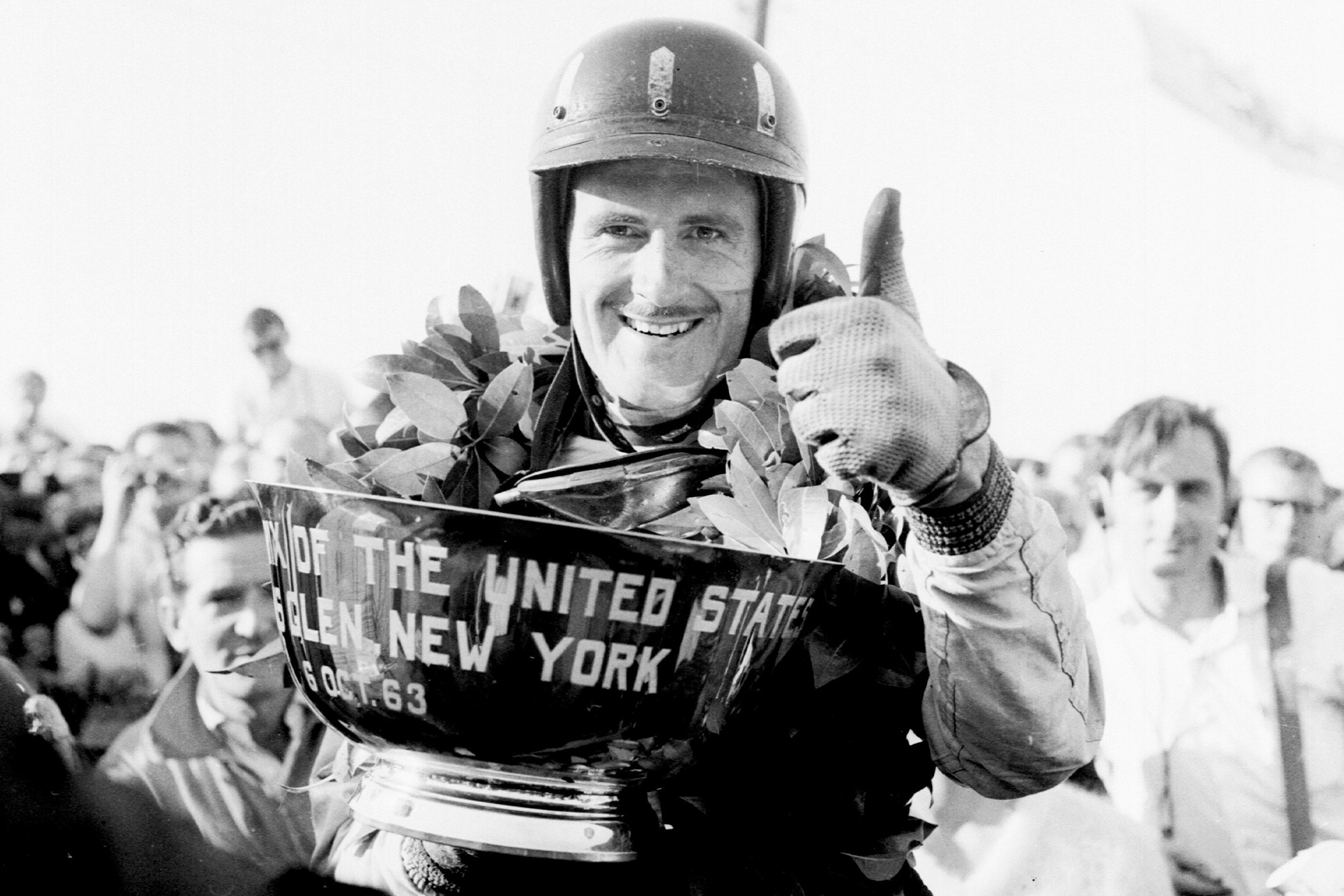 Graham Hill (BRM/Owen Racing Org.) celebrates his 1st position on the podium with a thumbs-up.