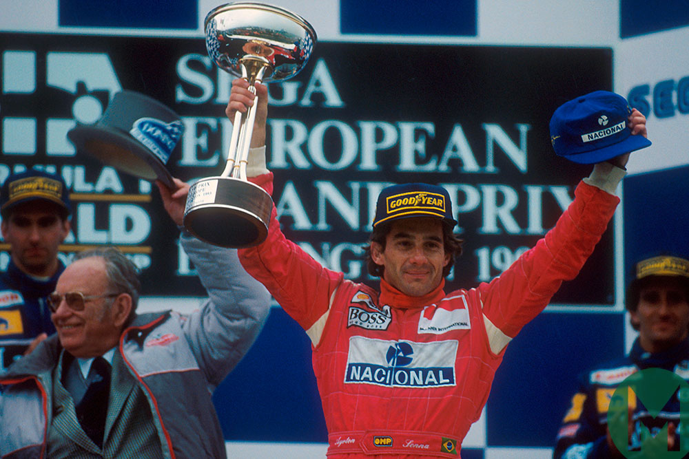 Ayrton Senna celebrates on the podium with Donington circuit owner Tom Wheatcroft