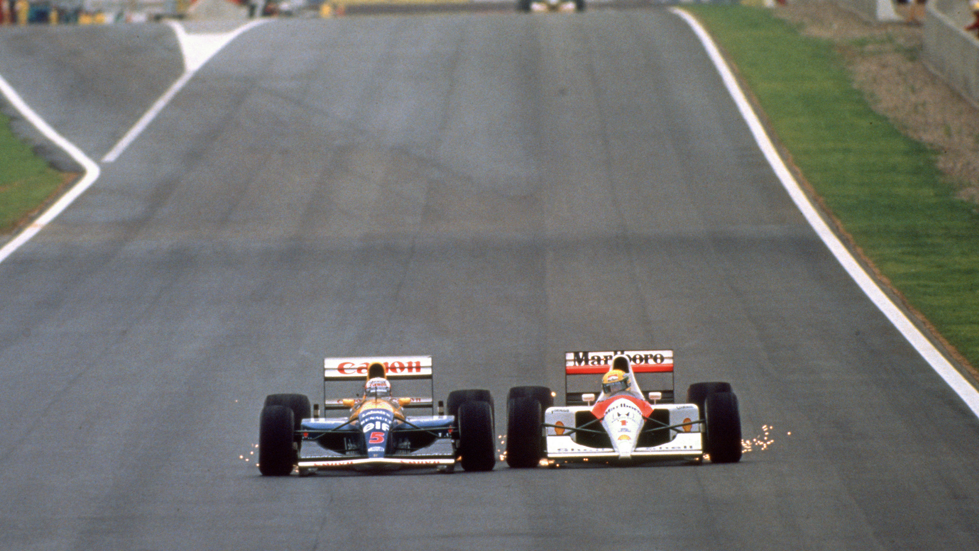 Nigel Mansell and Ayrton Senna are side by side with sparks flying during the 1991 Spanish Grand Prix