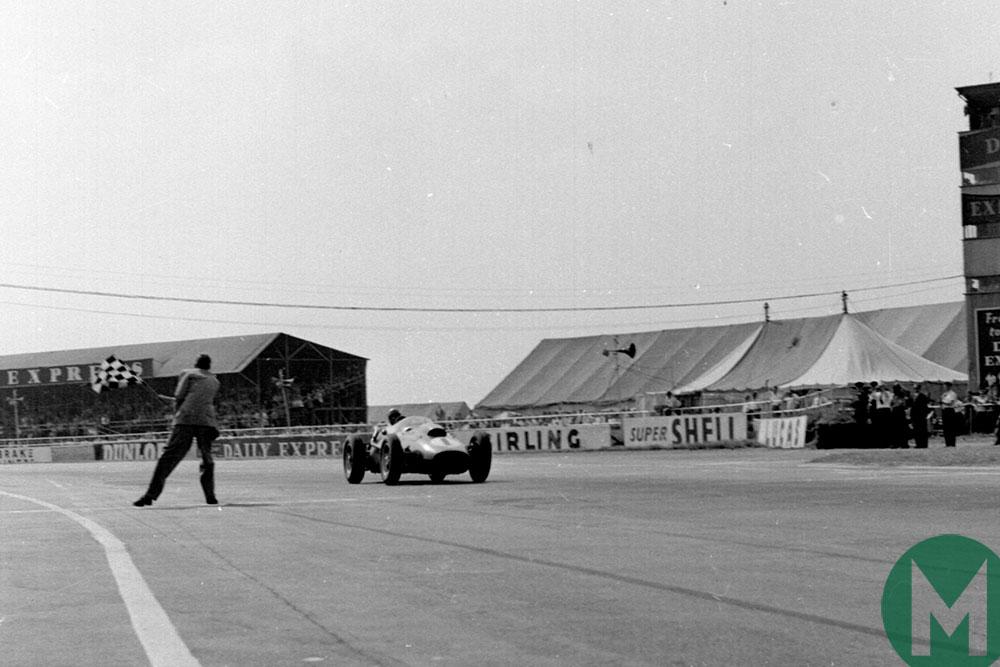 Peter Collins' Ferrari takes the flag in the 1958 British Grand Prix