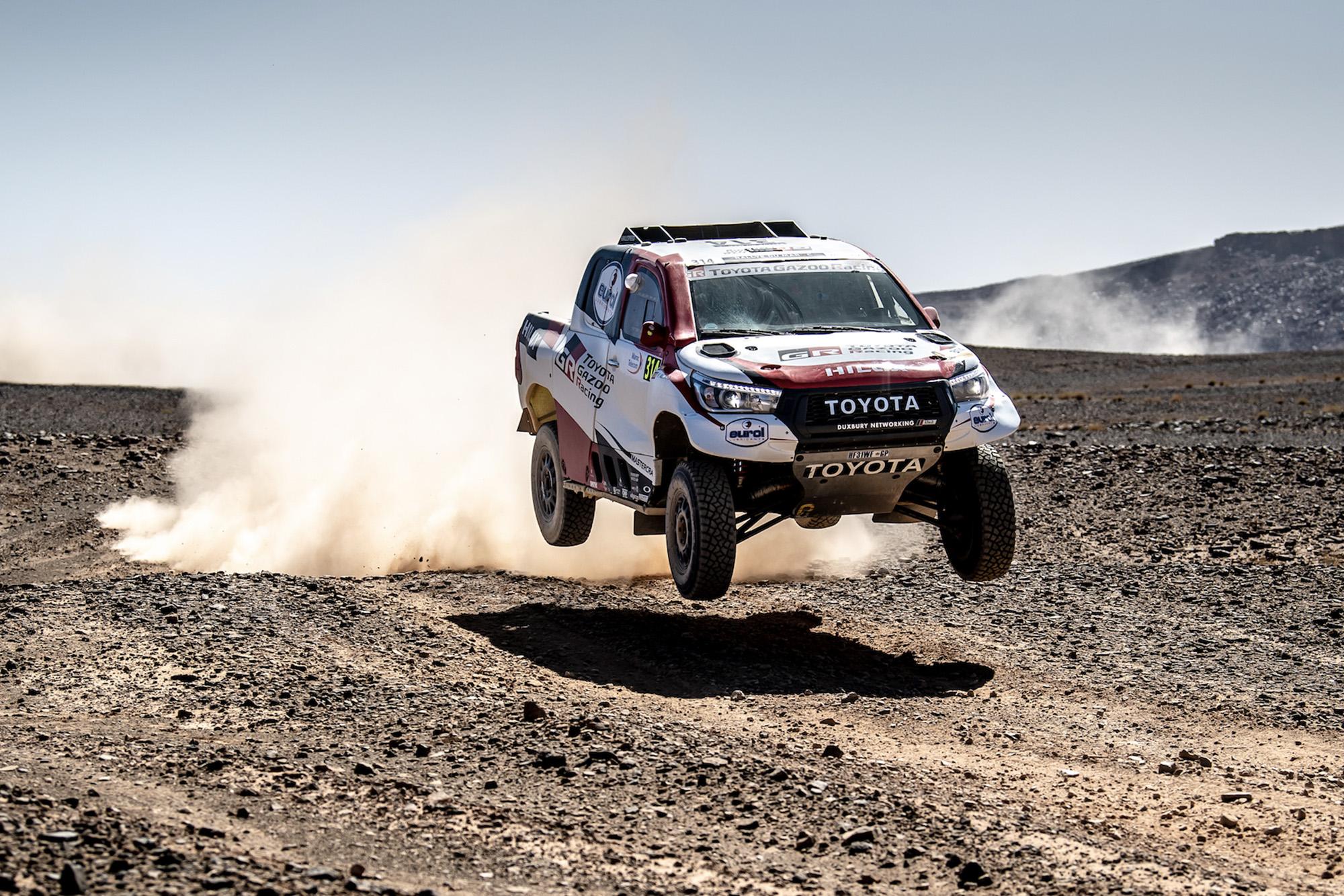 Fernando Alonso's Dakar-spec Toyota Hilix jumping over a rally raid course