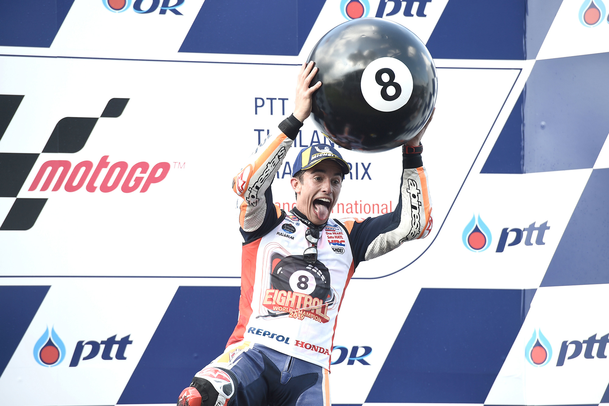 Marx Marquez on the podium with an 8 ball at the 2019 Thailand MotoGP race, after winning his sixth MotoGP title