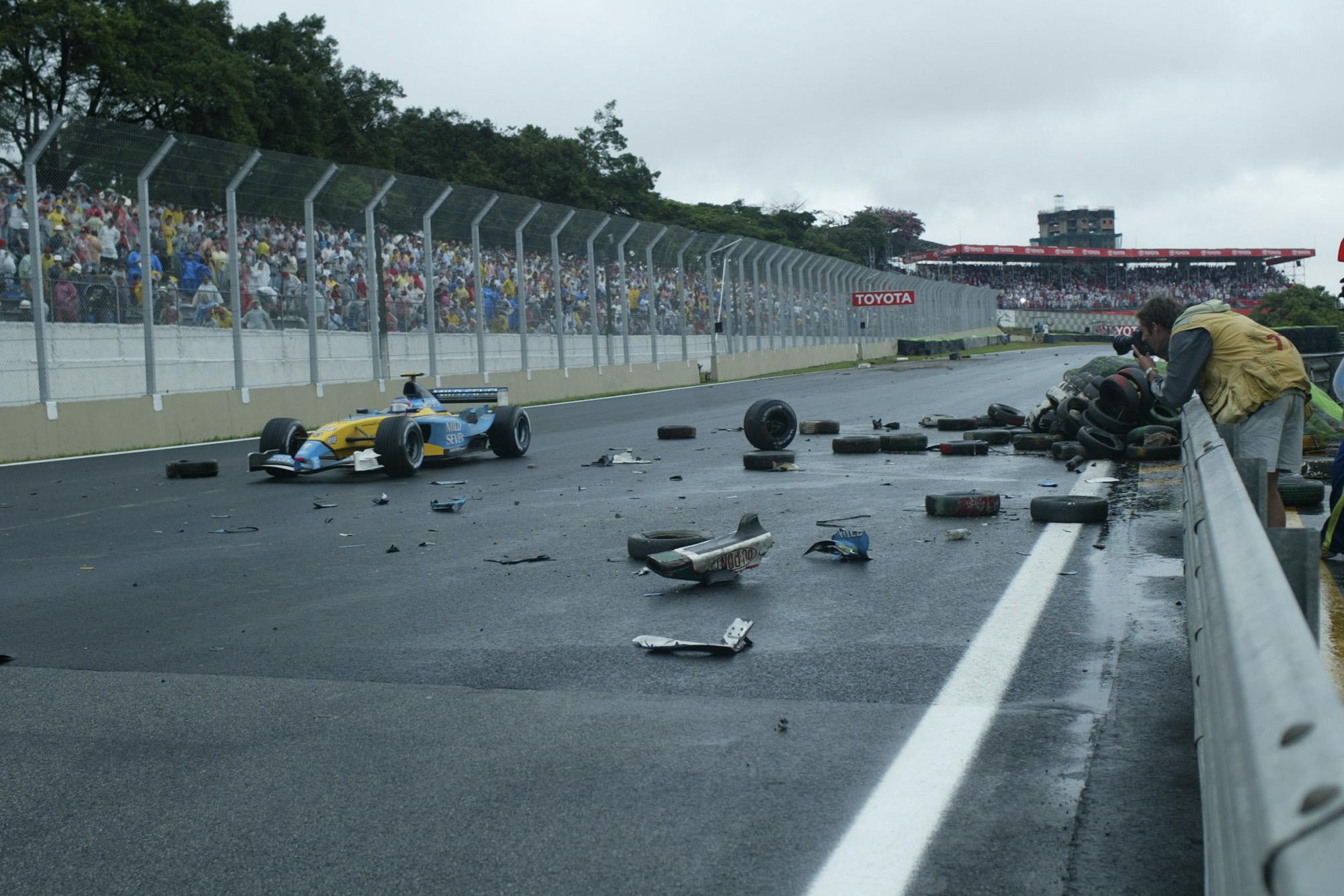 Jarno Trulli drives past crash debris in the 2003 F1 Brazilian Grand Prix