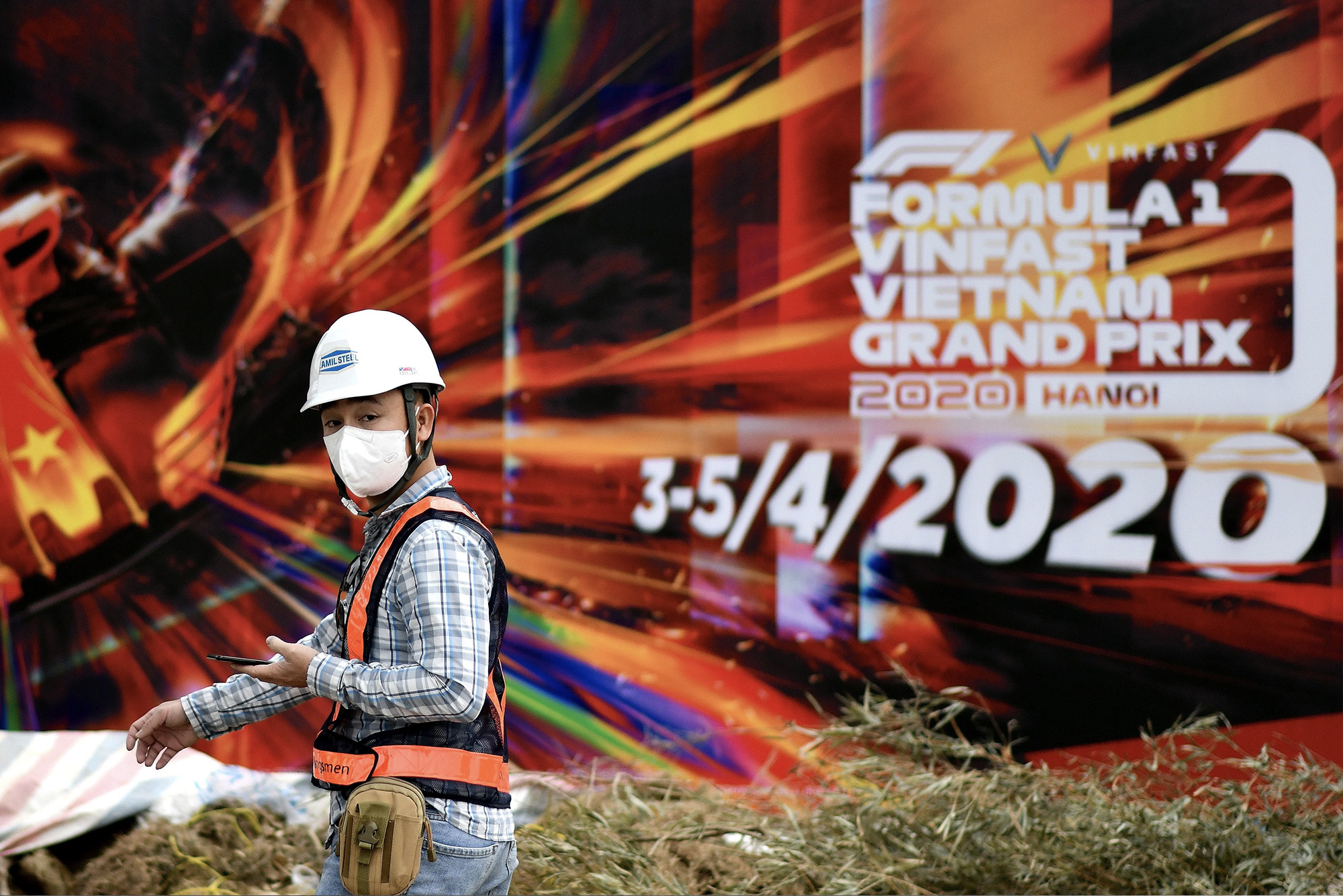 Worker with face mask in front of F1 Vietnamese Grand Prix poster