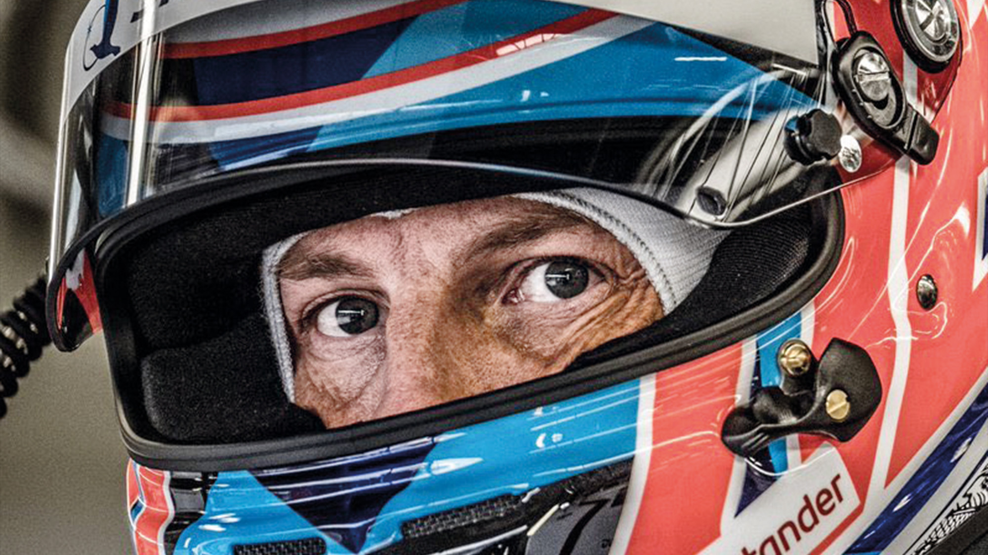 Jenson Button's eyes peer out from behind his helmet