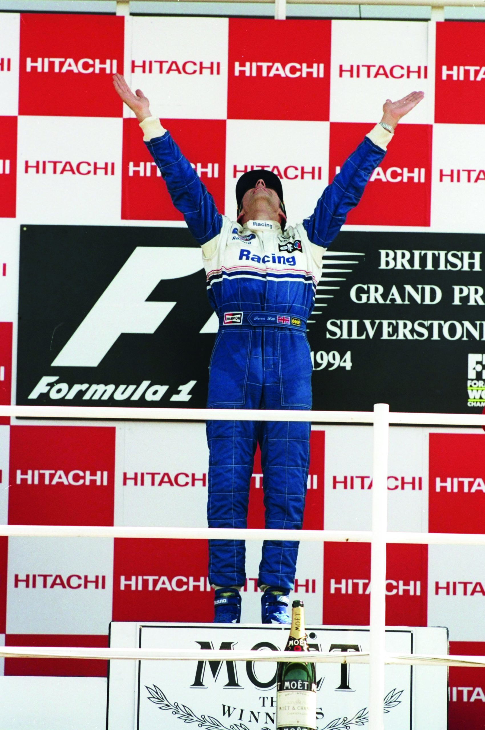 Damon-Hill-raises-his-hands-to-the-air-on-the-podium-after-winning-the-1994-F1-British-Grand-Prix-at-Silverstone