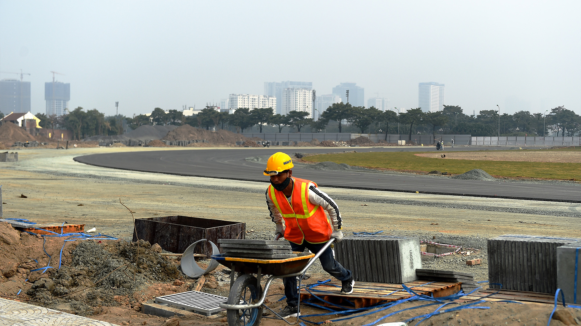 A worker with a wheelbarrow at the Hanoi Street Circuit in Vietnam
