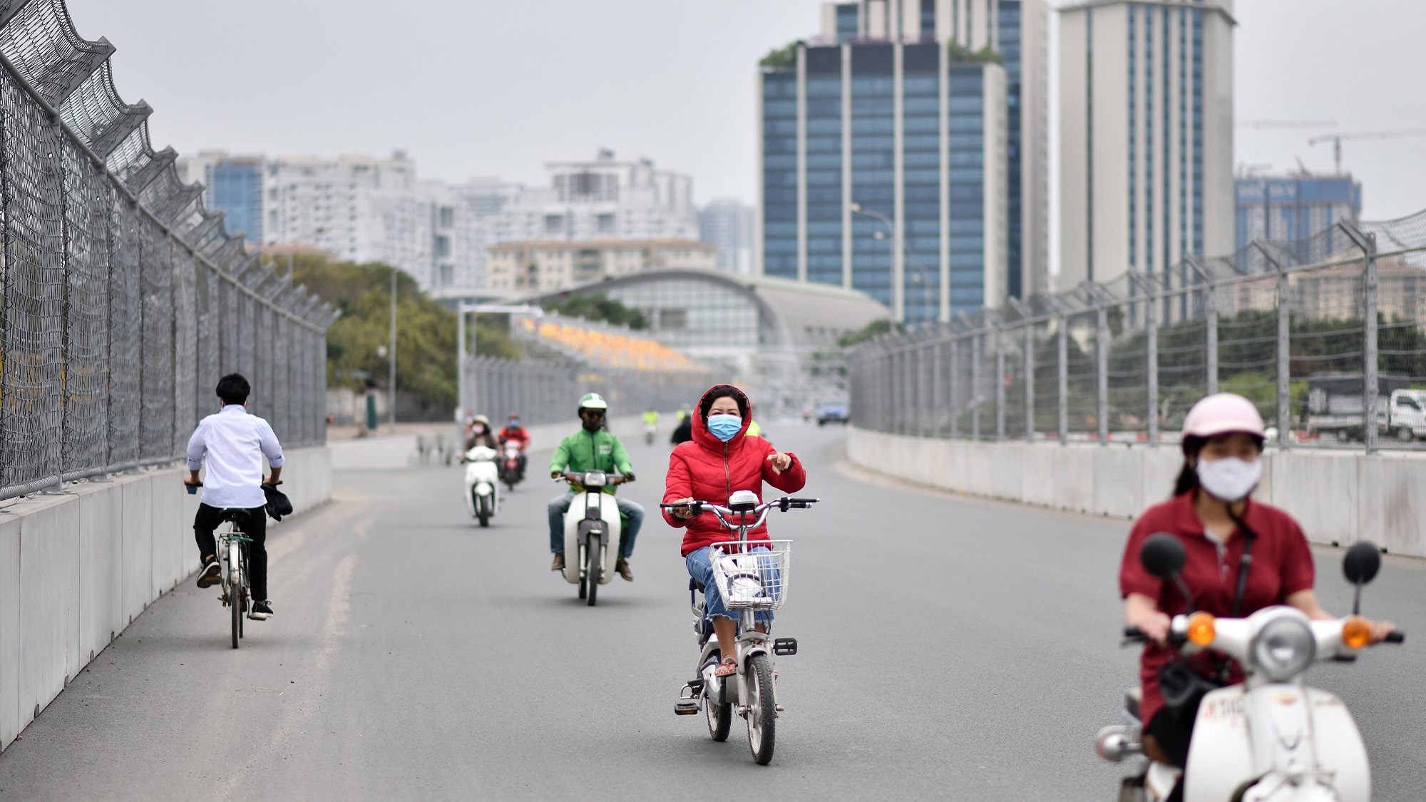Moped and bicycle riders travel on the Hanoi Street Circuit in Vietnam