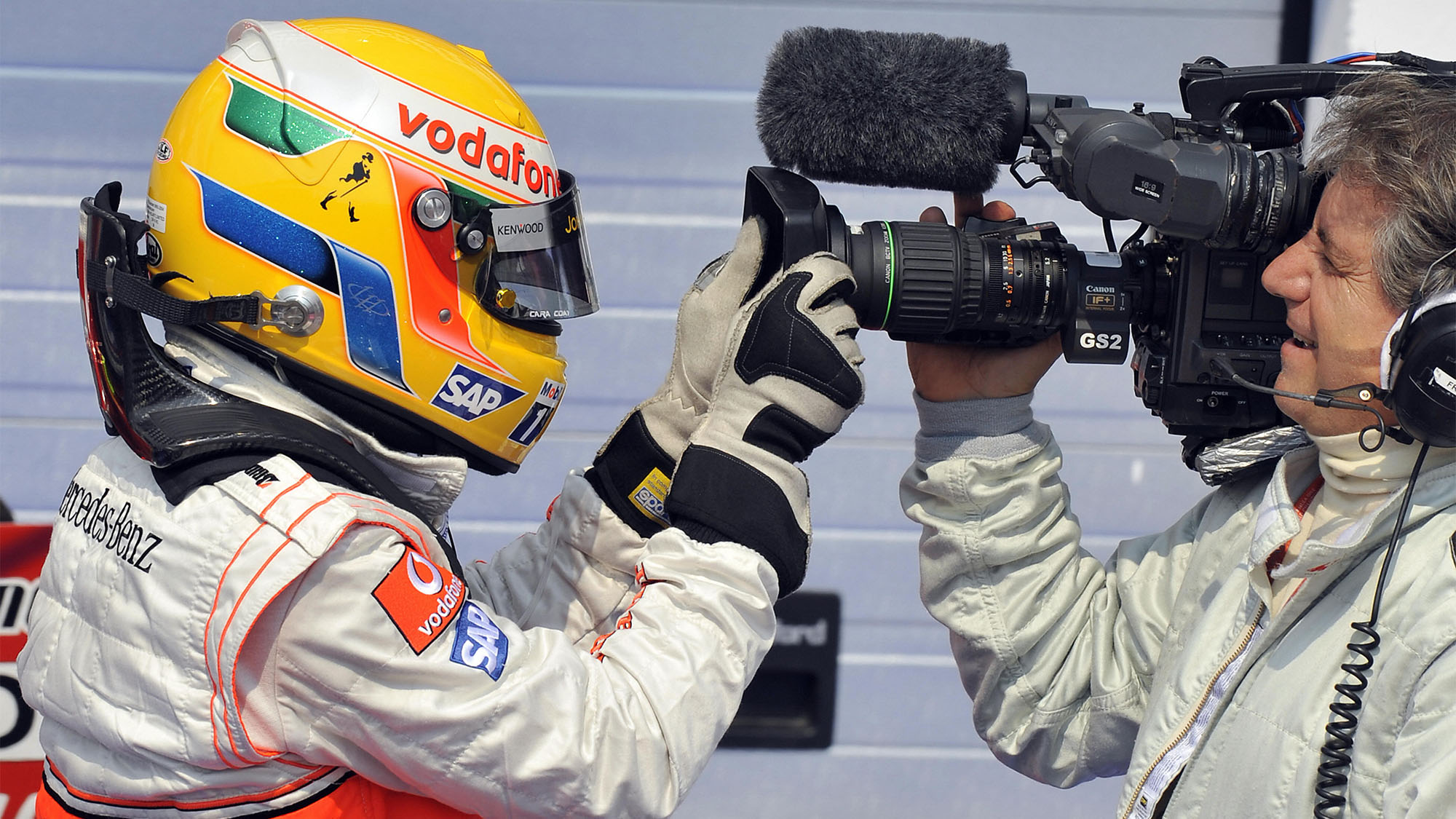 McLaren Mercedes' British driver Lewis Hamilton celebrates with a cameraman in the parc ferme of the Hungaroring racetrack on August 2, 2008 in Budapest after the qualifying session of the Formula One Hungarian Grand Prix. McLaren Mercedes' British driver Lewis Hamilton took the pole position ahead of his Finnish team mate Heikki Kovalainen and Ferrari Brazilian's driver Felipe Massa.
