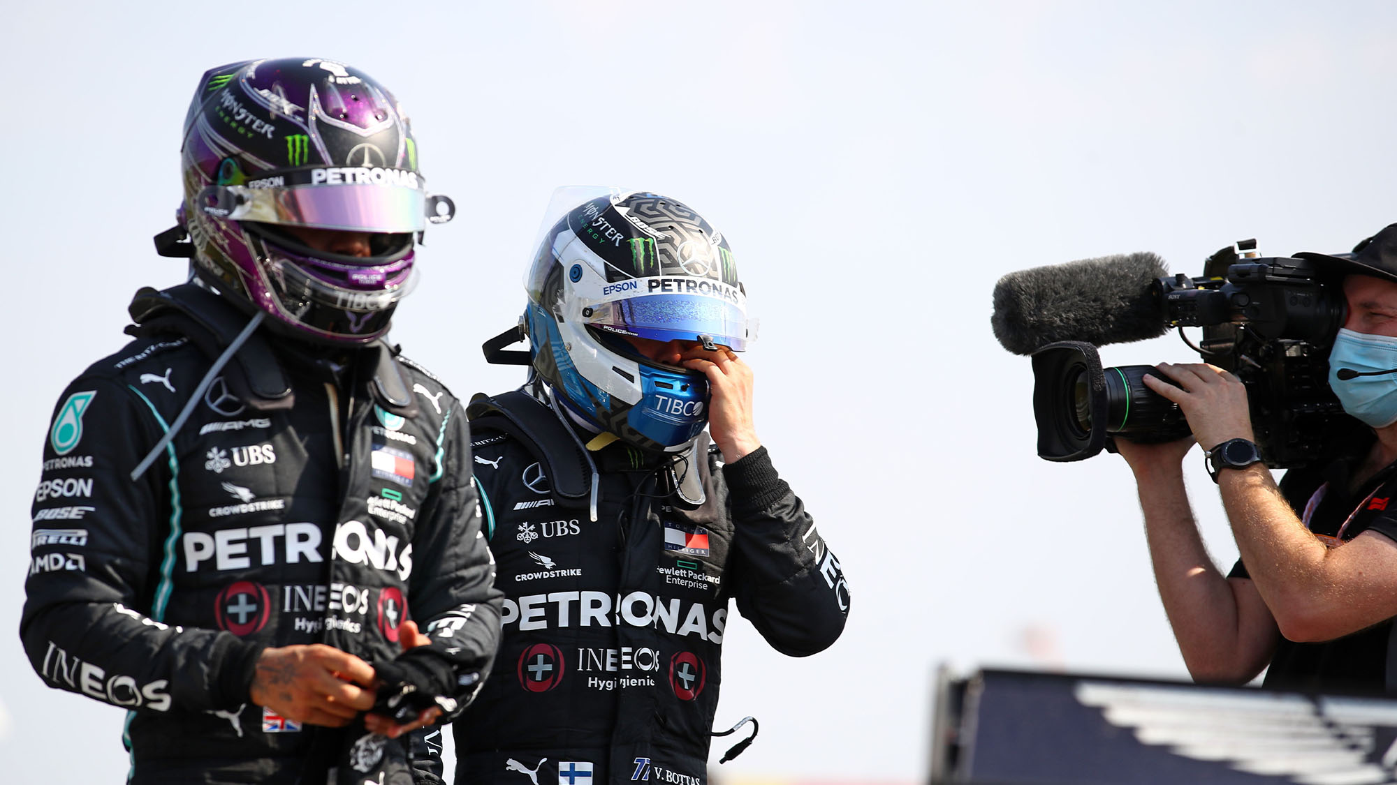 A cameraman follows Mercedes' British driver Lewis Hamilton (L) and Mercedes' Finnish driver Valtteri Bottas (C) as they walk to the podium at the end of the race during the F1 70th Anniversary Grand Prix at Silverstone on August 9, 2020 in Northampton. - The race commemorates the 70th anniversary of the inaugural world championship race, held at Silverstone in 1950. (Photo by Bryn Lennon / POOL / AFP) (Photo by BRYN LENNON/POOL/AFP via Getty Images)