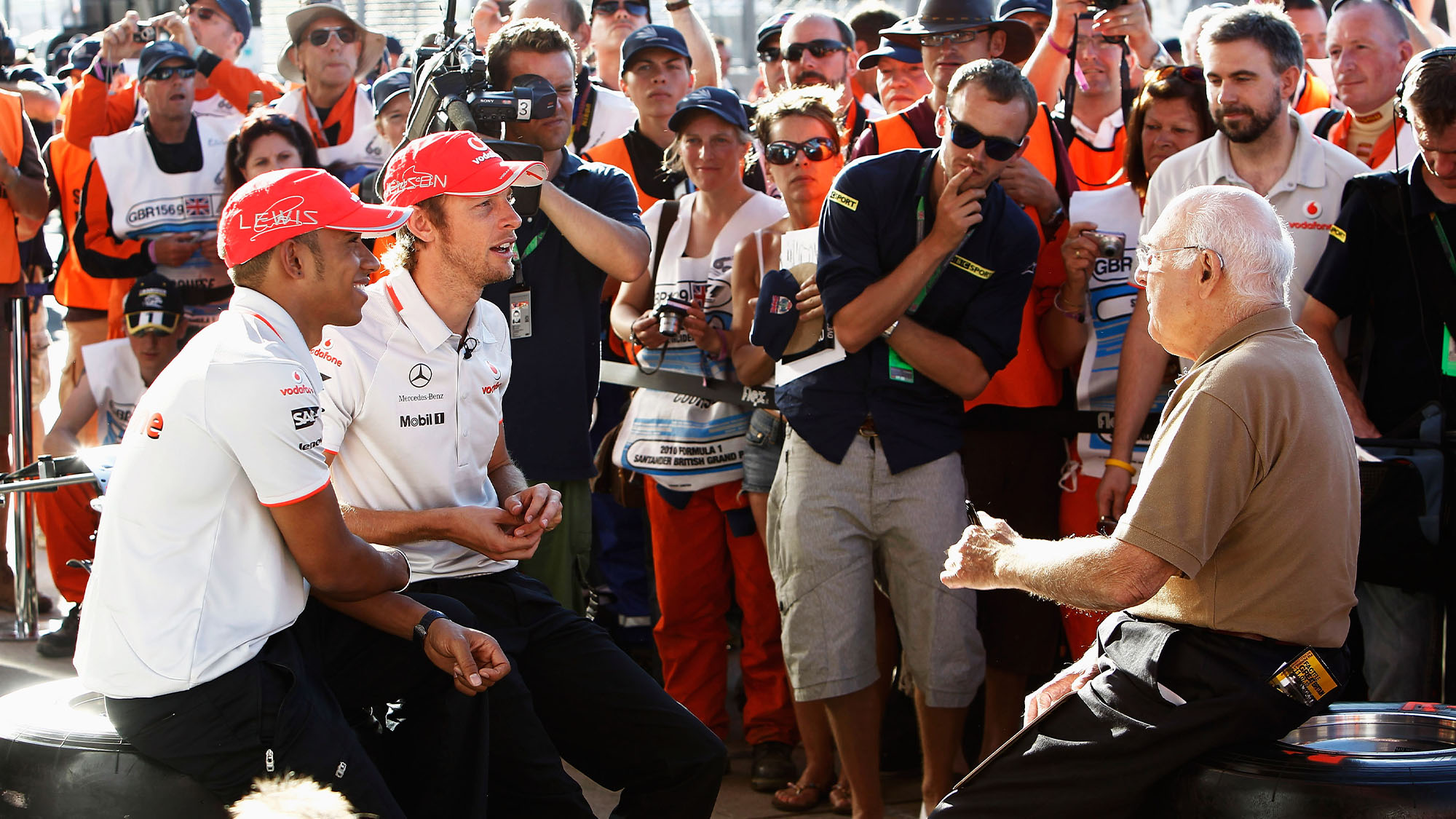 NORTHAMPTON, UNITED KINGDOM - JULY 10: Lewis Hamilton of Great Britain and McLaren Mercedes and Jenson Button of Great Britain and McLaren Mercedes are interviewed by Murray Walker following qualifying for the British Formula One Grand Prix at Silverstone Circuit on July 10, 2010, in Northampton, England. (Photo by Hoch Zwei/Getty Images)