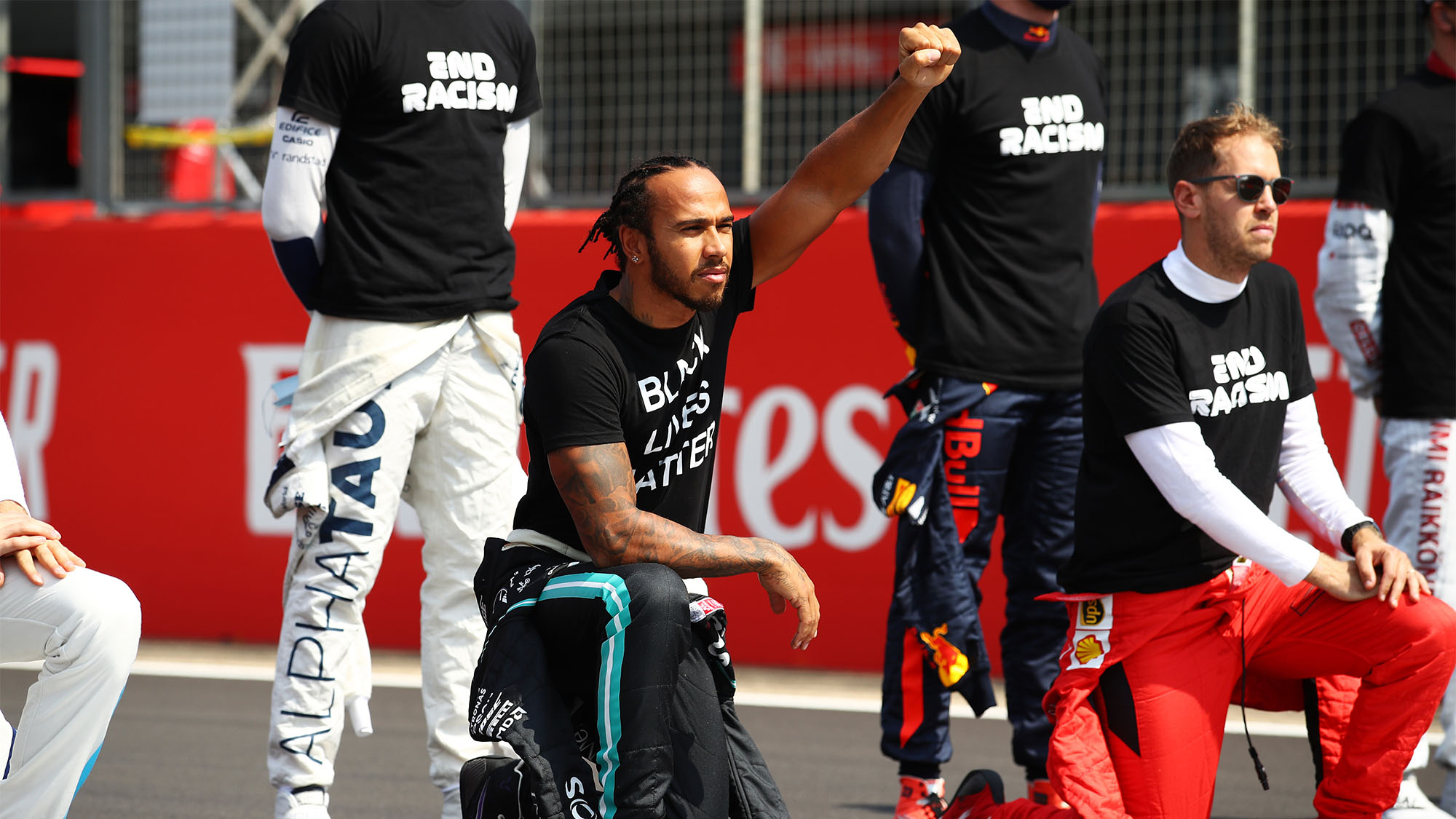NORTHAMPTON, ENGLAND - AUGUST 09: Lewis Hamilton of Great Britain and Mercedes GP takes a knee on the grid in support of the Black Lives Matter movement prior to the F1 70th Anniversary Grand Prix at Silverstone on August 09, 2020 in Northampton, England. (Photo by Bryn Lennon/Getty Images)