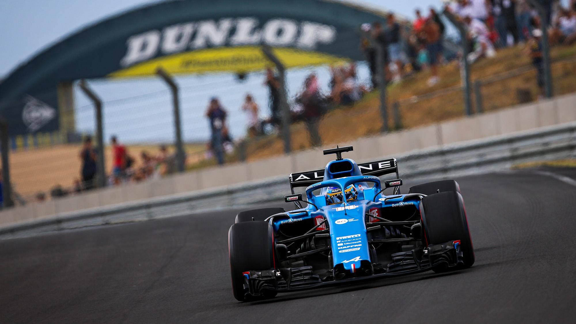 Fernando Alonso in Alpine F1 car in front of Le Mans Dunlop bridge