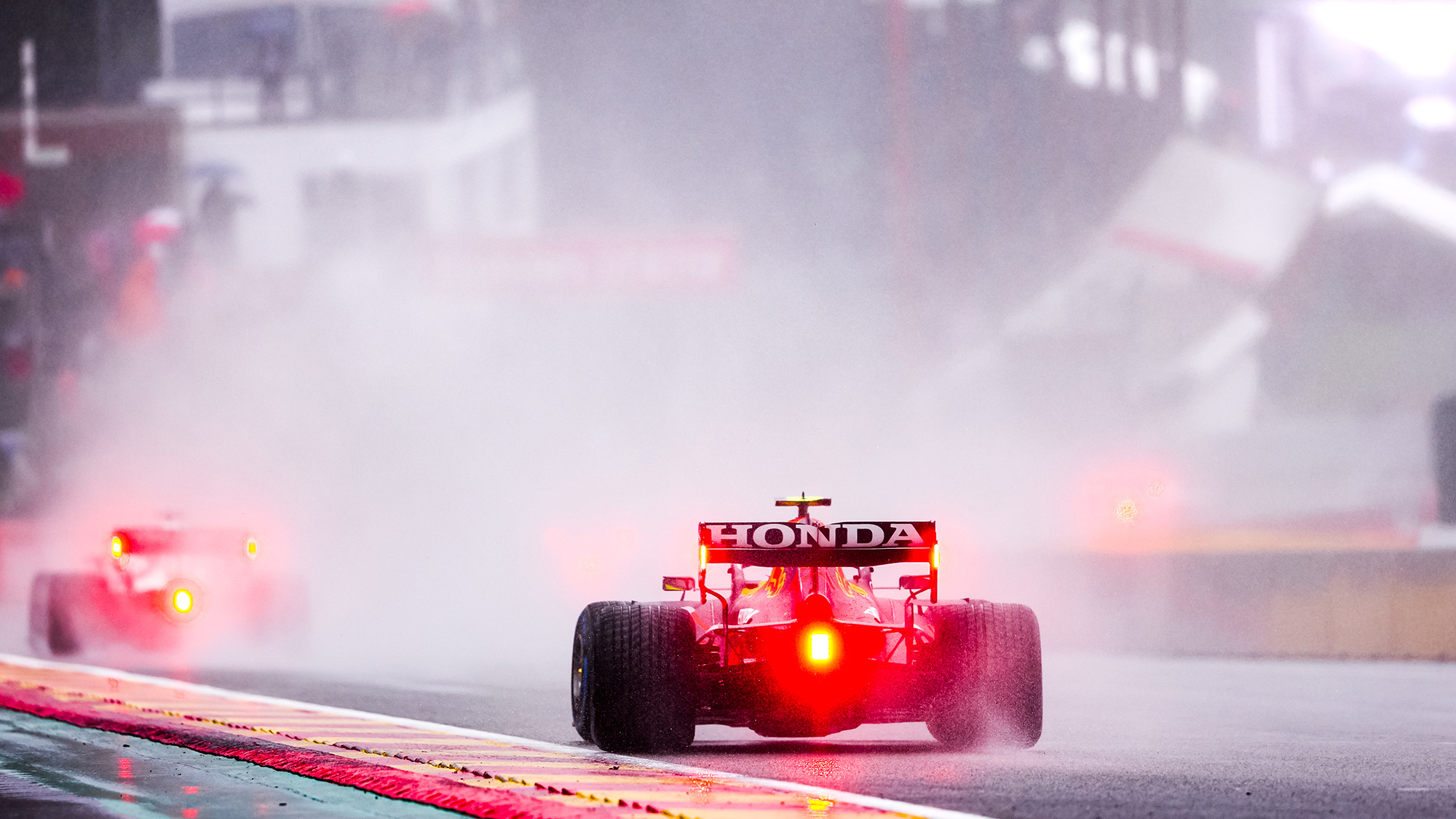 Red lights of F1 cars through the spray at the 2021 Belgian Grand Prix