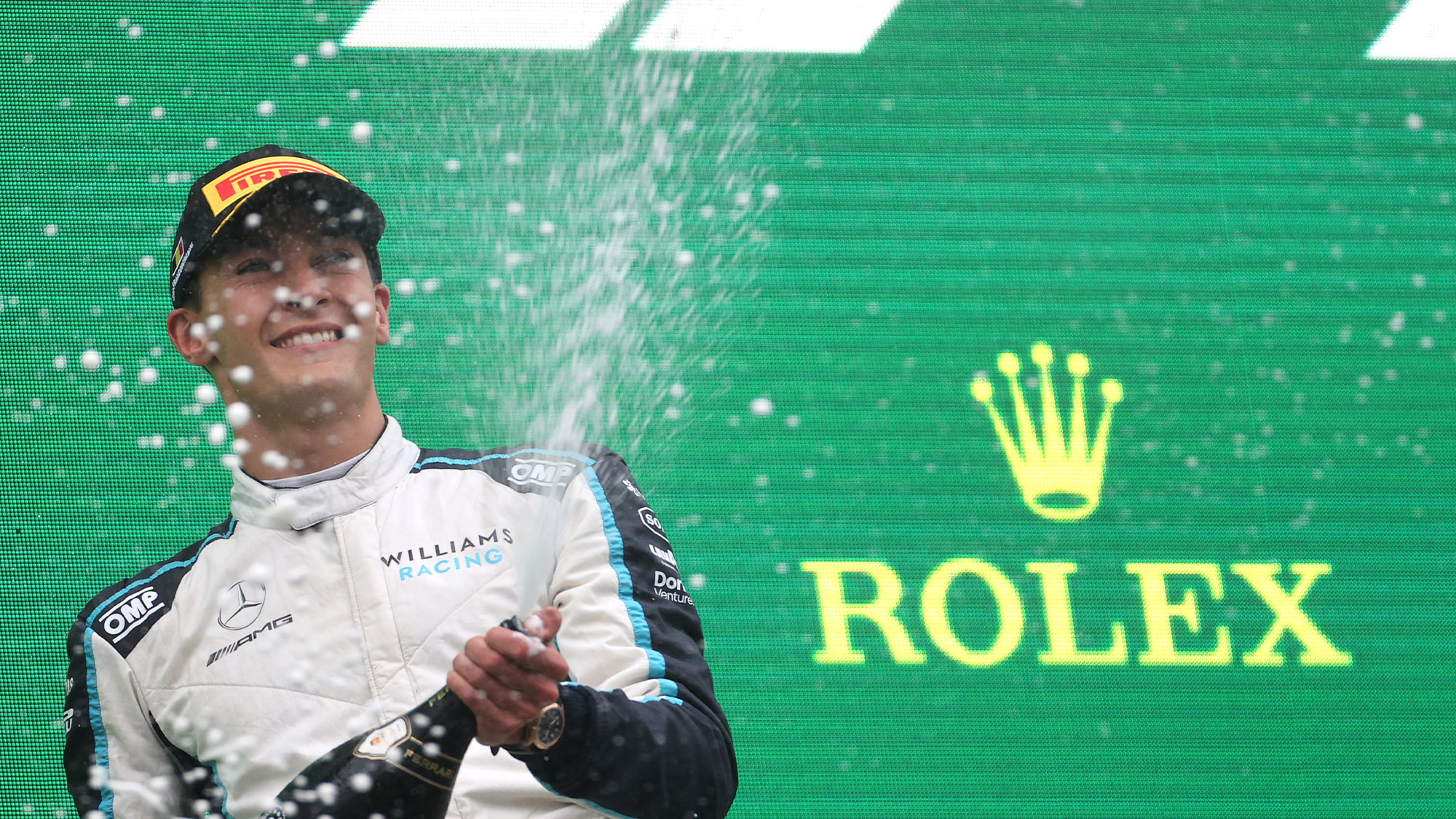 George Russell sprays champagne on the podium after the 2021 Belgian Grand Prix
