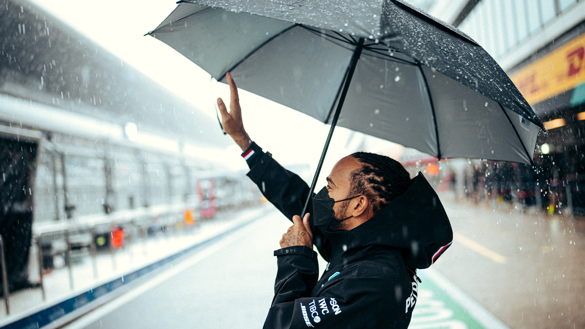 Lewis Hamilton waves to the crowd in wet Sochi