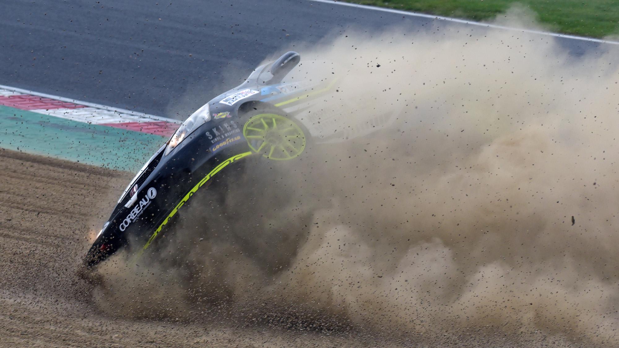 Honda Civic of Ben Sharpe rolls in the gravel at Brands Hatch