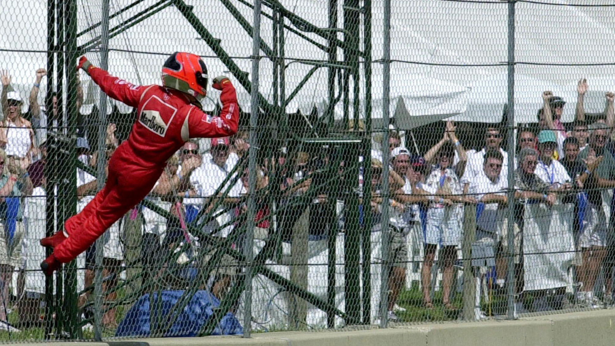 Spider Man Helio Castroneves climbs the fence at Ohio IndyCar race in 2000