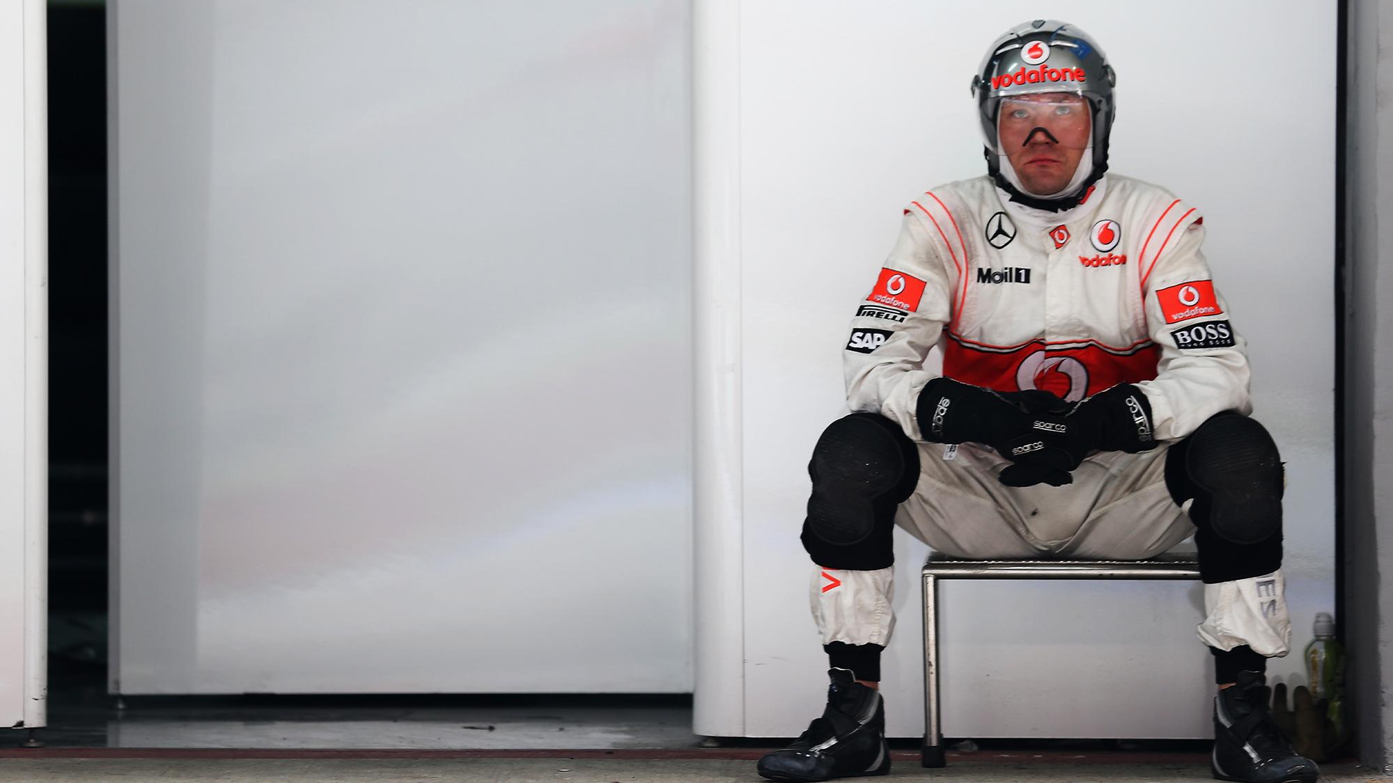 McLaren mechanic sits in the garage