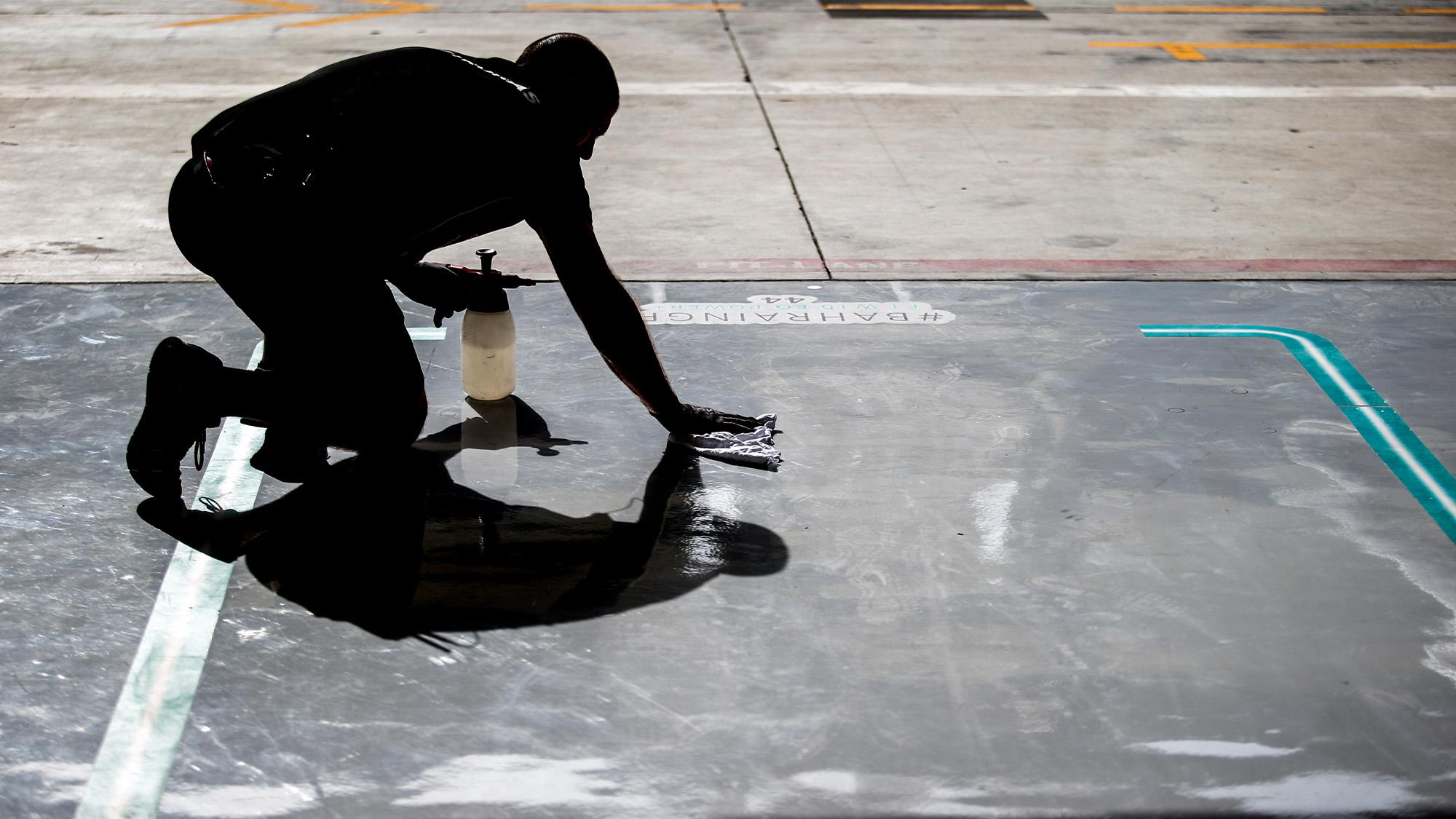 Mercedes Mechanic cleans the garage floor